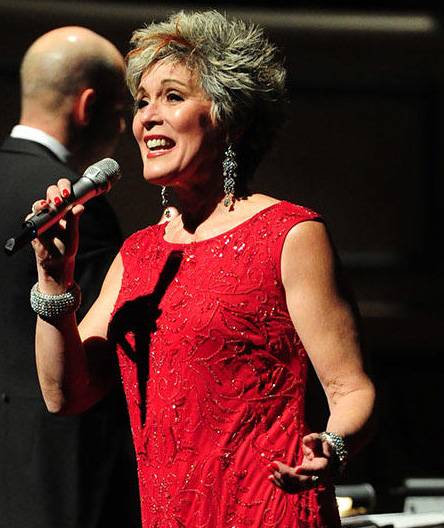 Sylvia McNair holding microphone, hand outstretched and singing