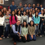 High school students standing with New West Symphony conductor