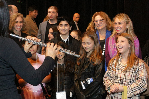 Kids smiling and watching flautist perform backstage