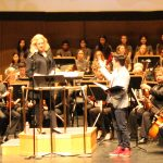 Symphonic Adventures conductor and host on stage with orchestra