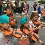 Three small girls trying out violins