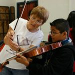 Teacher showing boy how to hold violin