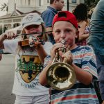 Young children playing trumpet and violin at festival